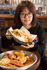 Ng Ye shows off two menu items at Red Crab Juicy Seafood in Pensacola, the fried shrimp basket and the lobster combo, which is also the Friday special and features a half snow crab cluster, a lobster tail, a half pound of shrimp, two potatoes and an ear of corn in Juicy's special sauce.