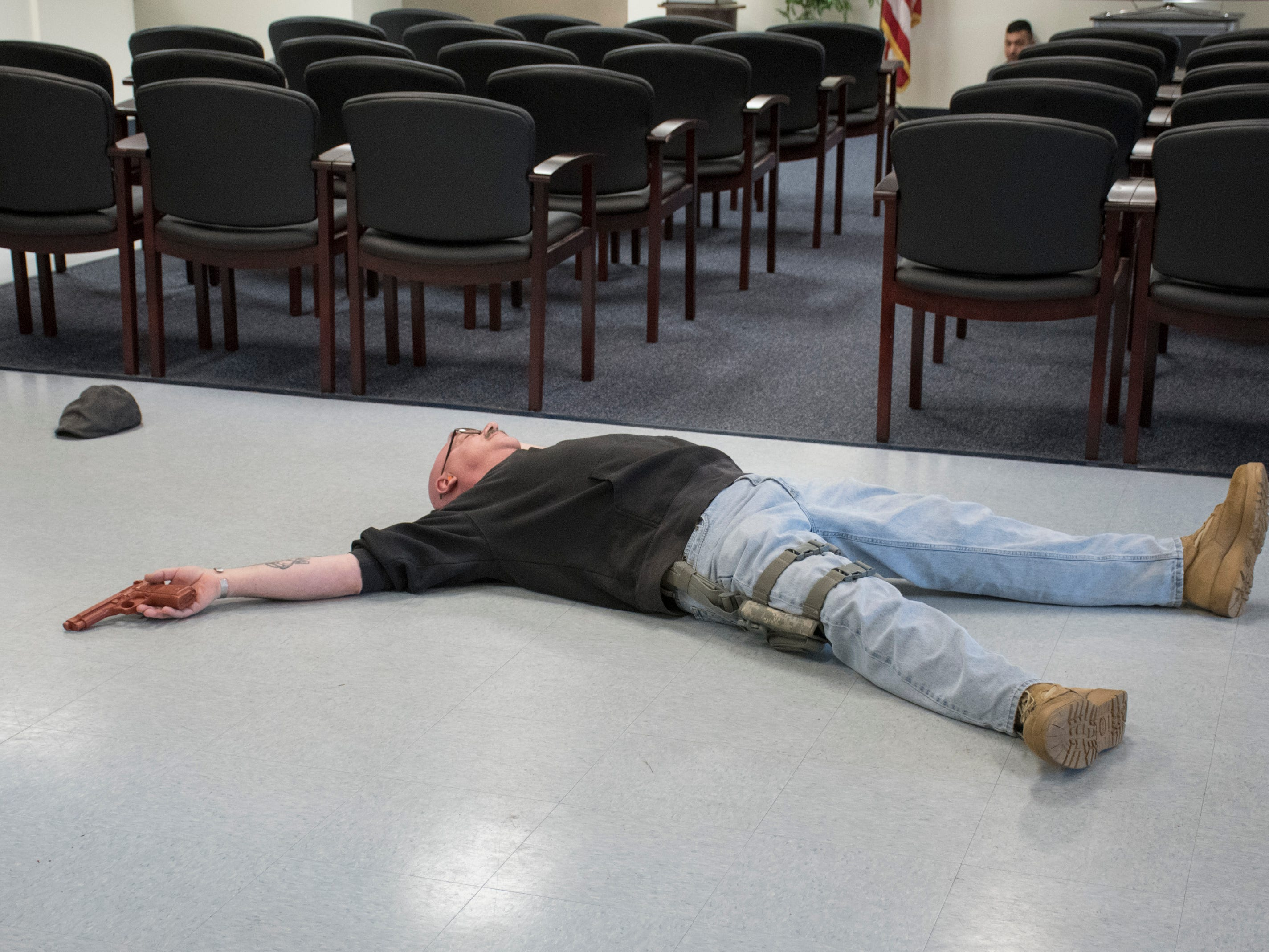 Portraying an armed intruder,  Senior Chief Aviation Structural Mechanic Pasquale Moreland lays on the ground after being shot in the Personnel Support Detachment building during Exercise Solid Curtain-Citadel Shield, an annual security exercise is conducted at NAS Pensacola on Tuesday, February 4, 2019.
