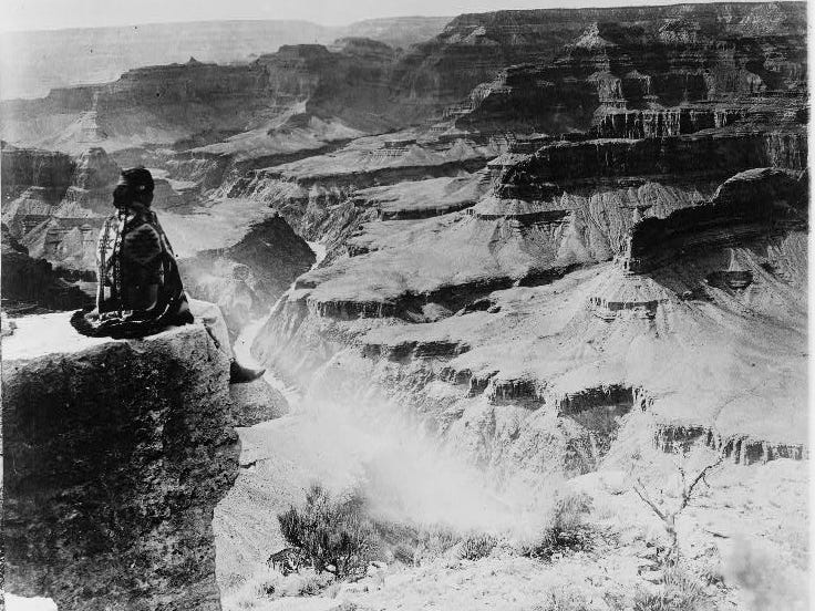 A member of the Hopi tribe sits on the edge of the Grand Canyon, ca. early 1900s.