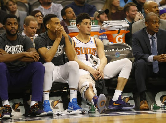 Phoenix Suns guard Devin Booker (1) watches the final moments of the fourth quarter against the Houston Rockets from the bench in Phoenix Feb. 4, 2019.