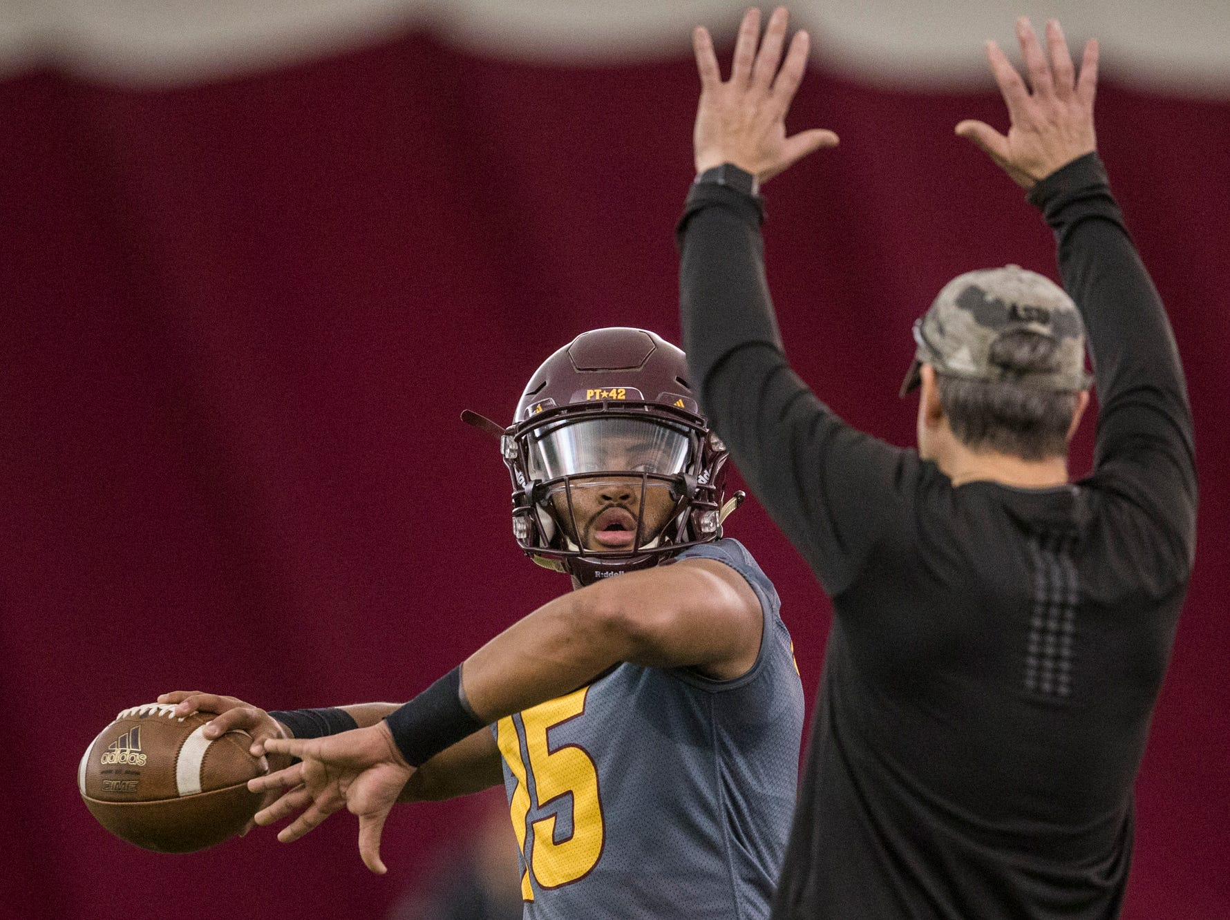 Dillon Sterling-Cole throws as offensive coordinator Rob Likens pressures him during practice on Tuesday, Feb. 5, 2019, at the Verde Dickey Dome in Tempe, Ariz.