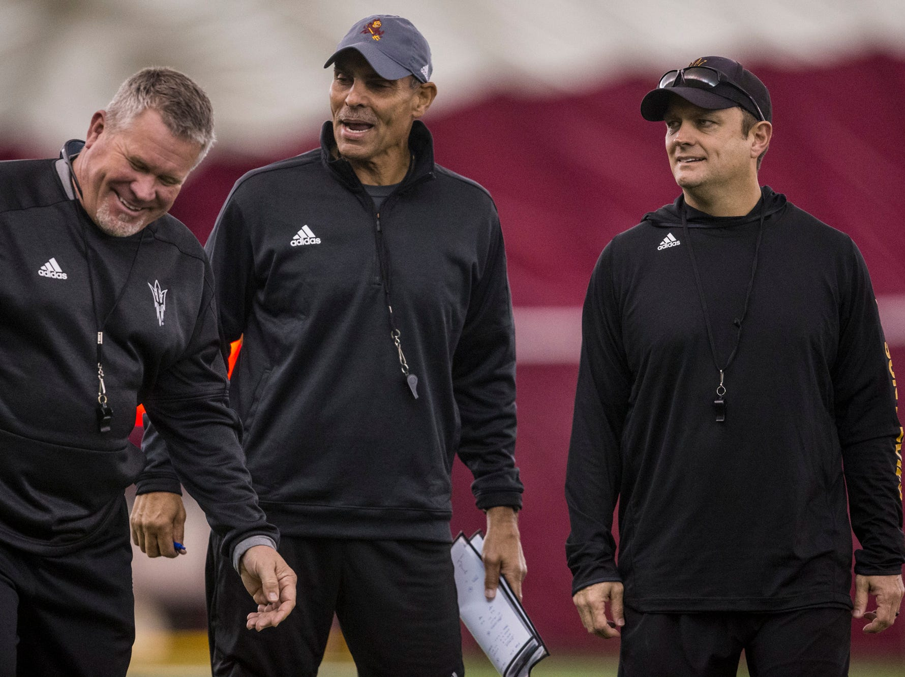 Head coach Herm Edwards talks with special teams coordinator Shawn Slocum (left) and defensive coordinator Danny Gonzales (right) during practice on Tuesday, Feb. 5, 2019, at the Verde Dickey Dome in Tempe, Ariz.