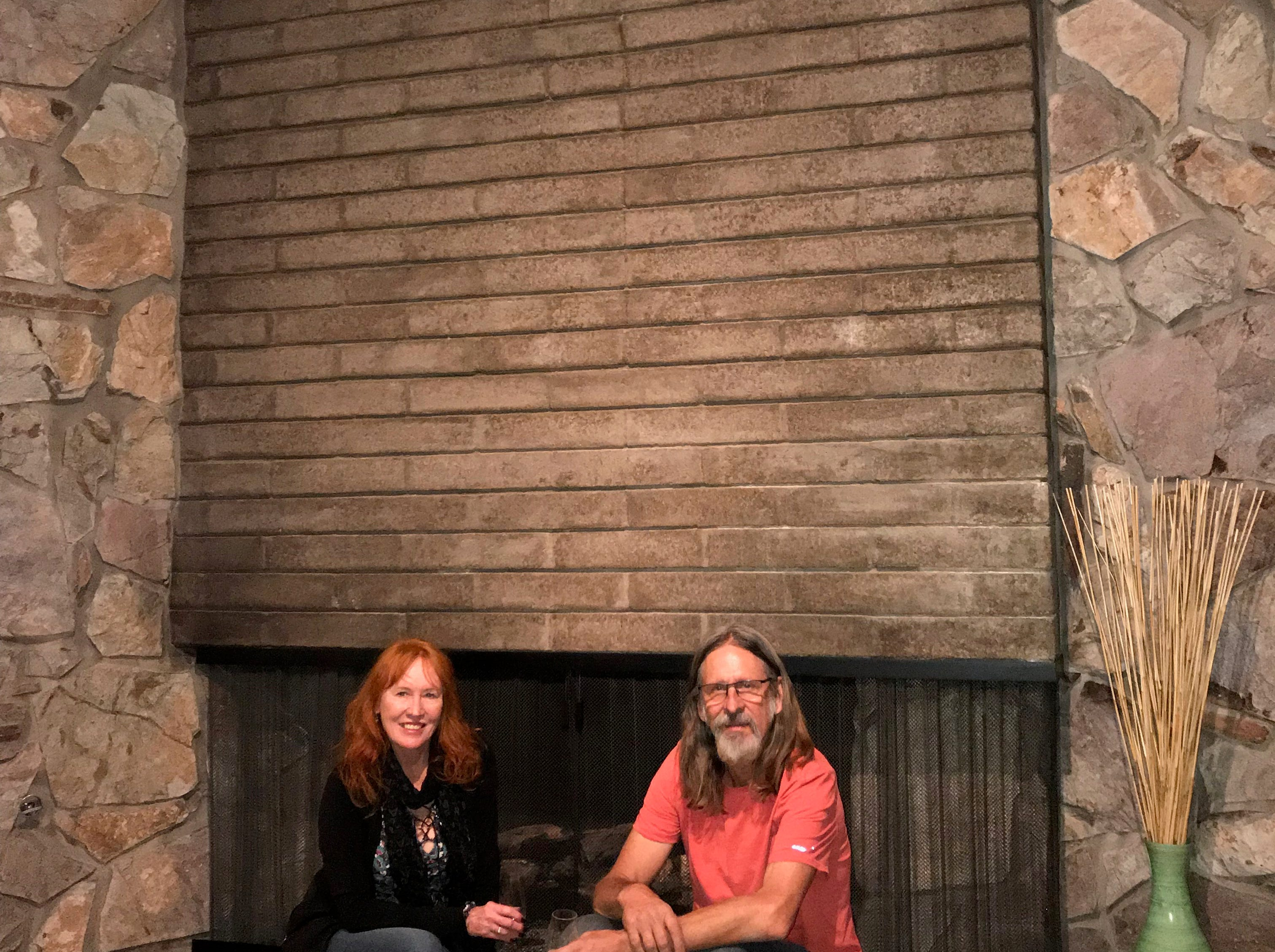 Owners Thomasina and William Burke sit in front of the brick and stonework of their fireplace.