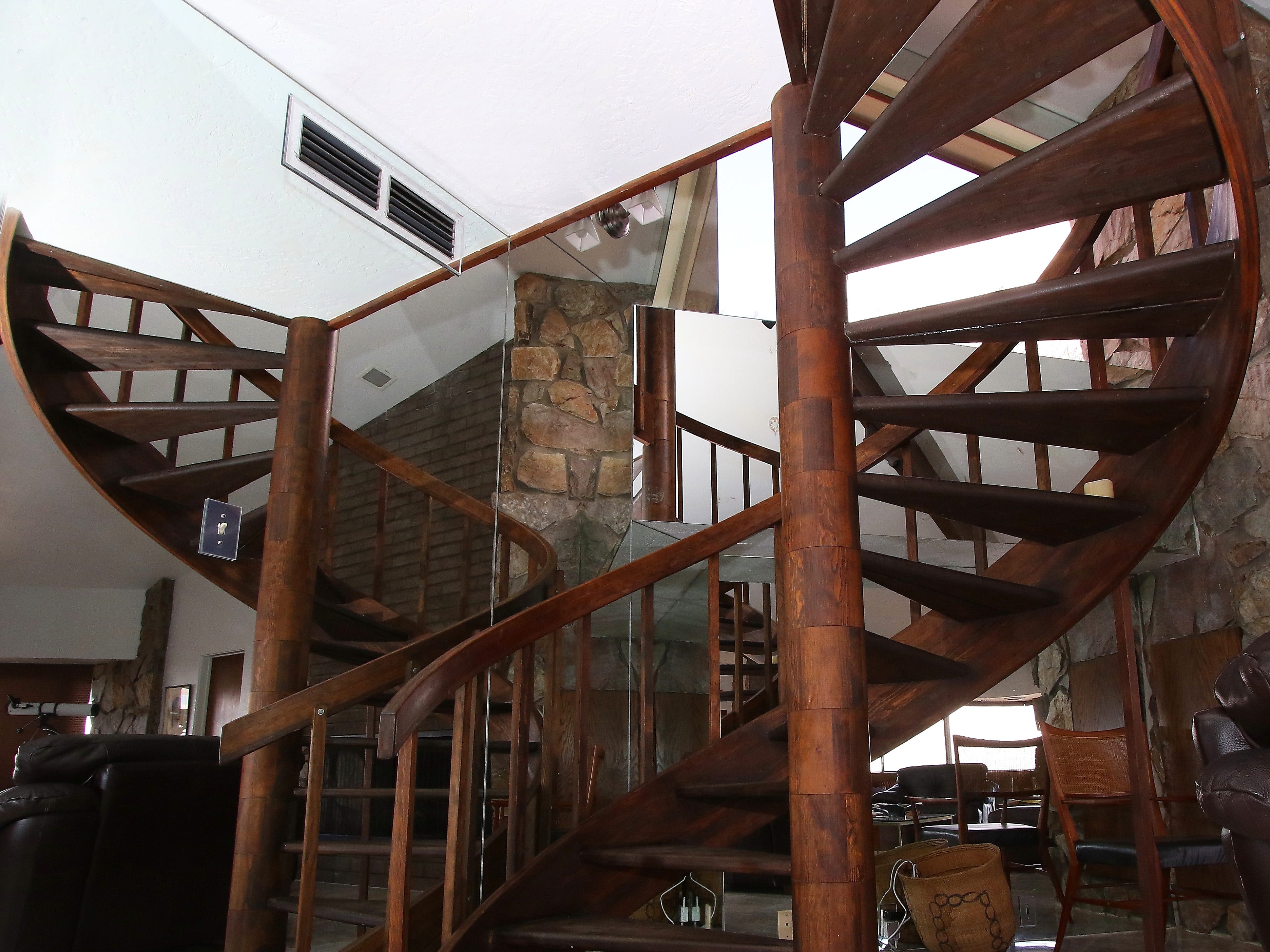 The wooden spiral staircase is set off by a backdrop of mirrors to make it appear as a series of staircases.