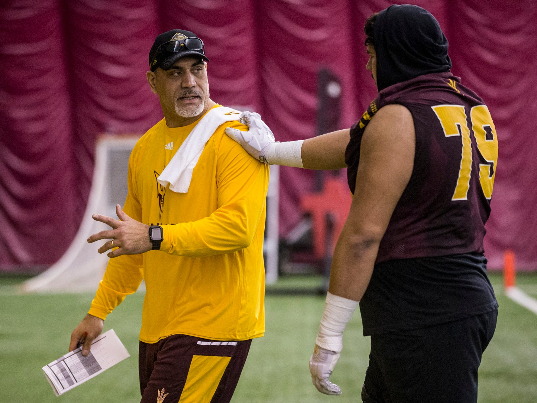 Offensive analyst Kevin Mawae works with Ralph Frias practice on Tuesday, Feb. 5, 2019, at the Verde Dickey Dome in Tempe, Ariz.