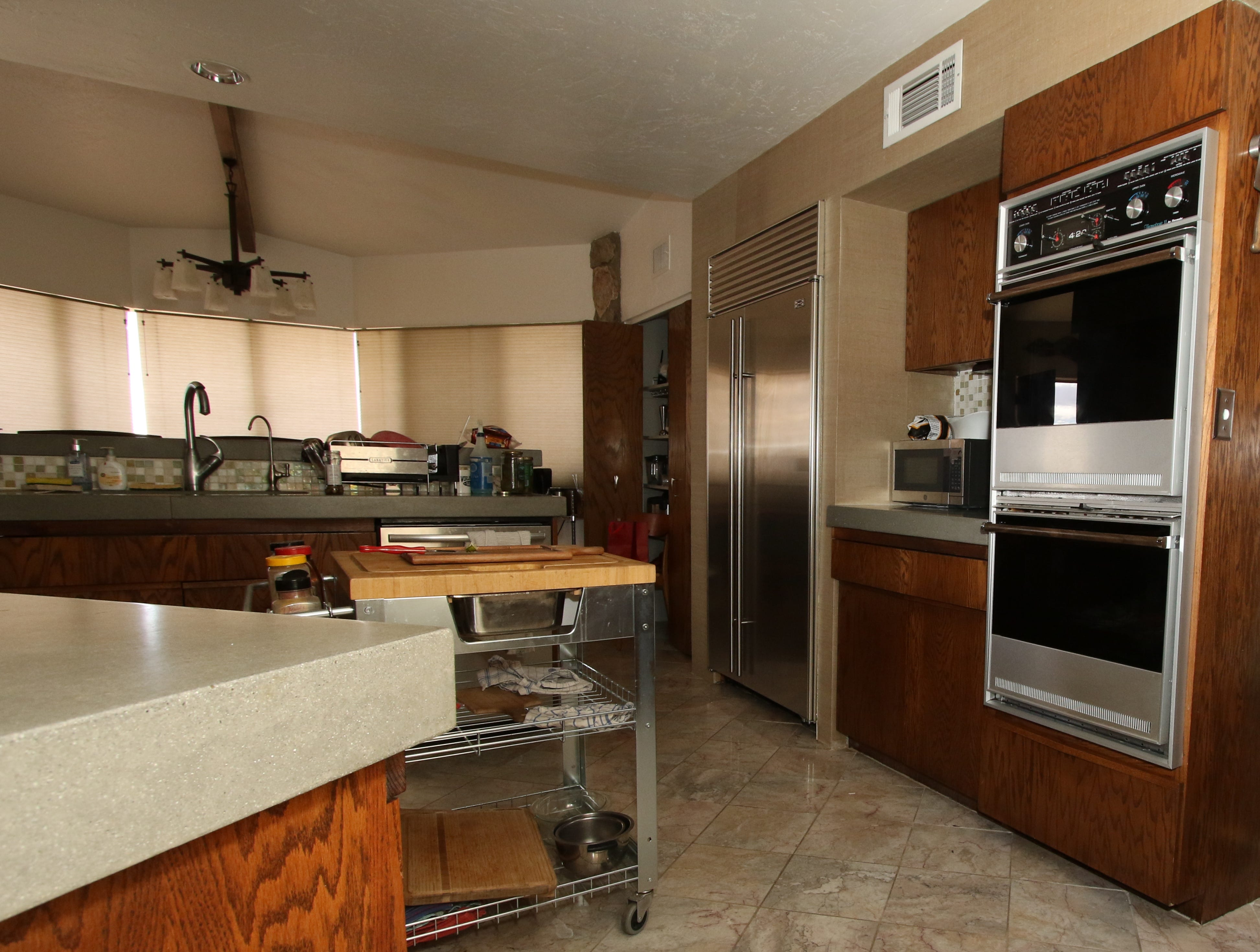 The kitchen features thick, polished, concrete counters with Frank Lloyd Wright embellishments. It also contains the original appliances and cabinetry.