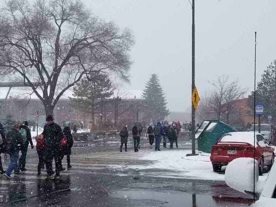 Students on the Northern Arizona University campus walk through the snowfall on Feb. 5, 2019, in Flagstaff.