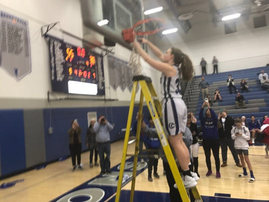 Hannah Woelfling takes her turn at cutting down the net.
