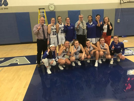 The Cedar Crest girls basketball team's players and coaches celebrate their third Section 1 title in the last four years Monday night after a clinching 55-38 win against Penn Manor.