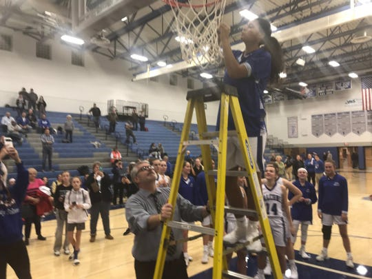 Cedar Crest's Raven Morgan snips off a piece of the net to celebrate Cedar Crest clinching the Section 1 title on Monday night.