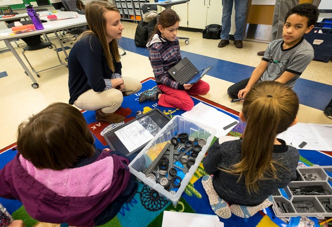 STEAM Academy at Woodrow Wilson third grade teacher Emily Hall works with a group of students to help them use their knowledge of simple machines to build a complex machine Tuesday, Feb. 5, 2019 in the STEAM portion of their class.