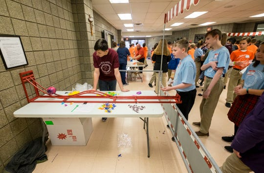 Cardinal Mooney Catholic High School sophomore Ben Strzyinski, left, helps a group of students in one of the games Tuesday, Feb. 5, 2019 during the school's Catholic Schools Week celebration.