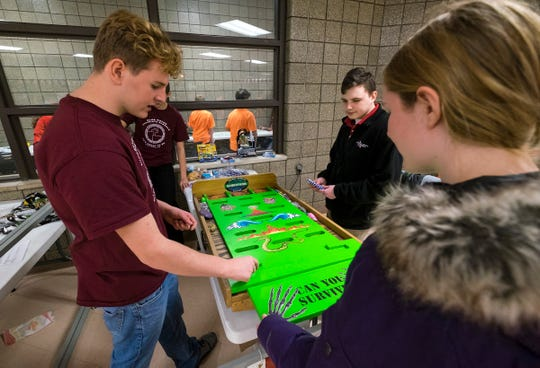 Cardinal Mooney Catholic High School junior James Van Daele, left, helps a group of students in one of the games Tuesday, Feb. 5, 2019 during the school's Catholic Schools Week celebration.