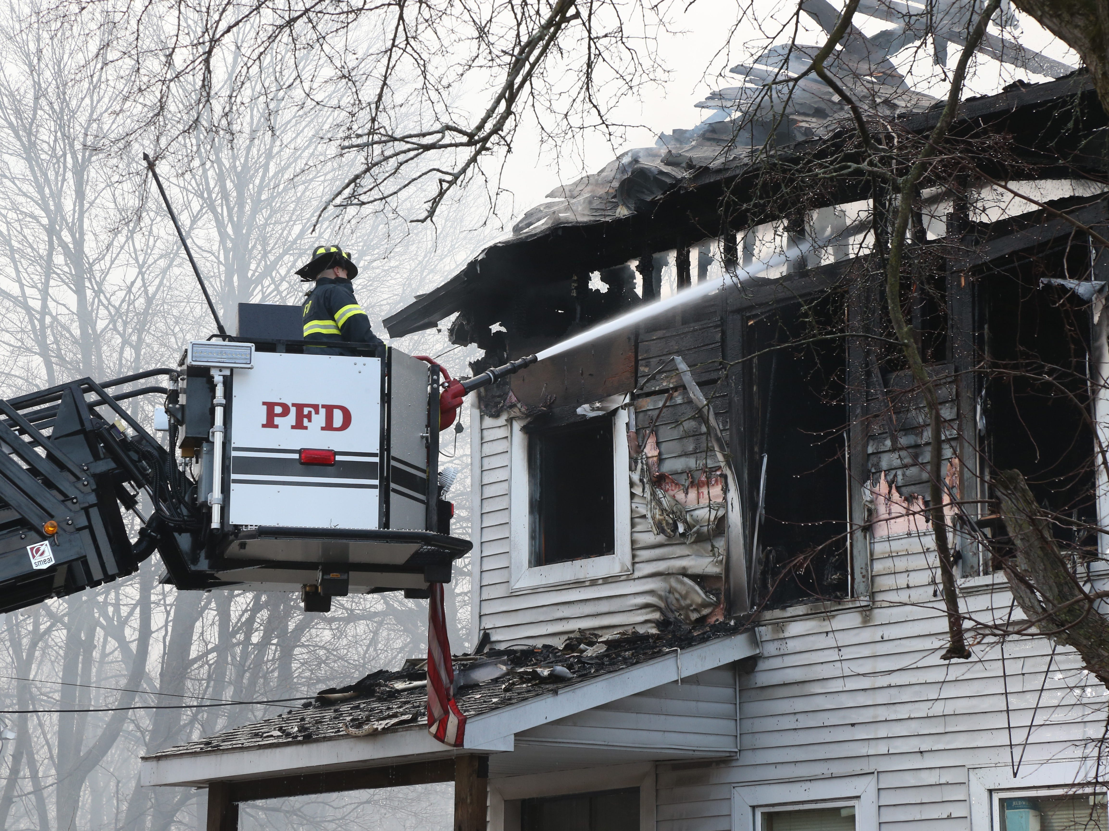 Poughkeepsie Fire Department Tower Ladder 2 dowses the 4 family building on Winnikee Avenue after battling back the fire in the City of Poughkeepsie on Feb. 5, 2019.