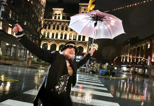 Roving entertainer Krystal Younglove dances in the rain during the New Year's Eve Countdown event at Continental Square Monday, Dec. 31, 2018. The white rose drop accompanied the countdown to midnight to usher in 2019. Bill Kalina photo