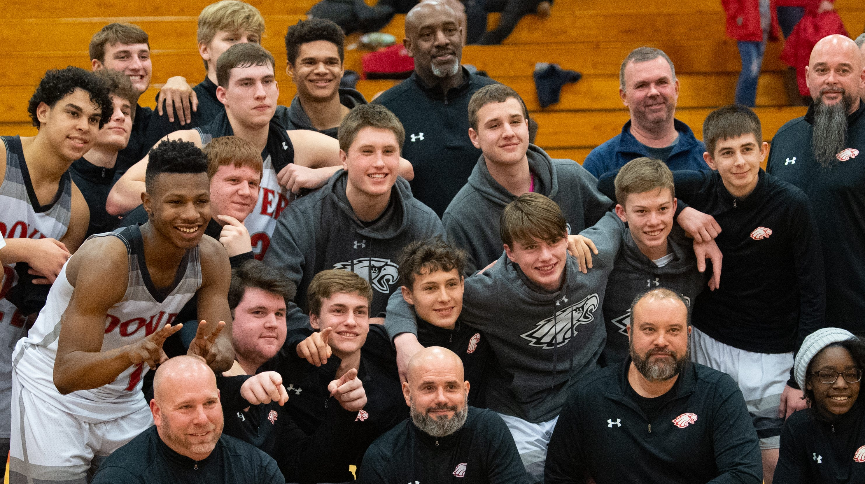 After receiving a plaque, scrapbook and signed basketball, Dover head coach Brian Schmoyer took a picture with the entire team, February 1, 2019.