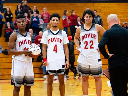 In this file photo from the 2018-19 season, Victor Dorm (11), Keith Davis (4) and Elijah Sutton (22) prepare to present a ball with signatures from the team to head coach Brian Schmoyer, who stepped down at the end of the season.