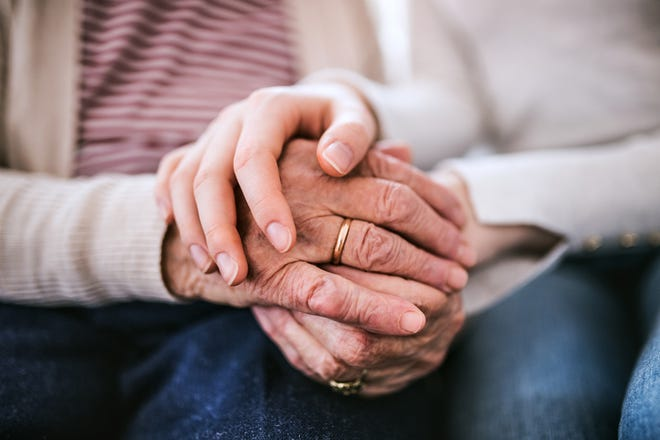 Unrecognizable teenage girl with grandmother at home, holding hands. Family and generations concept. Close up.