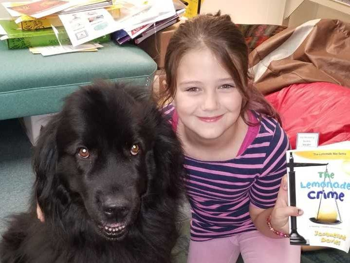 Students at Neil Armstrong School in Gates, like third-grader Evelyn Greene, can spend time reading to the school's therapy dog, Kelsey.