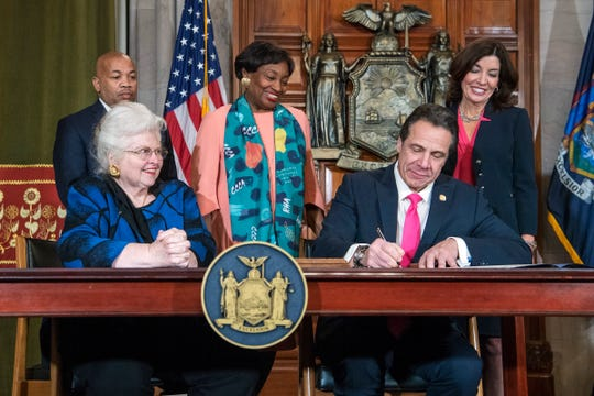 Gov. Andrew M. Cuomo, Cuomo, right, signs Reproductive Health Act Legislation during a ceremony, Tuesday, Jan. 22, 2019, in the Red Room at the State Capitol in Albany, N.Y. He is seated with Sarah Weddington, an attorney in the Roe v. Wade case.