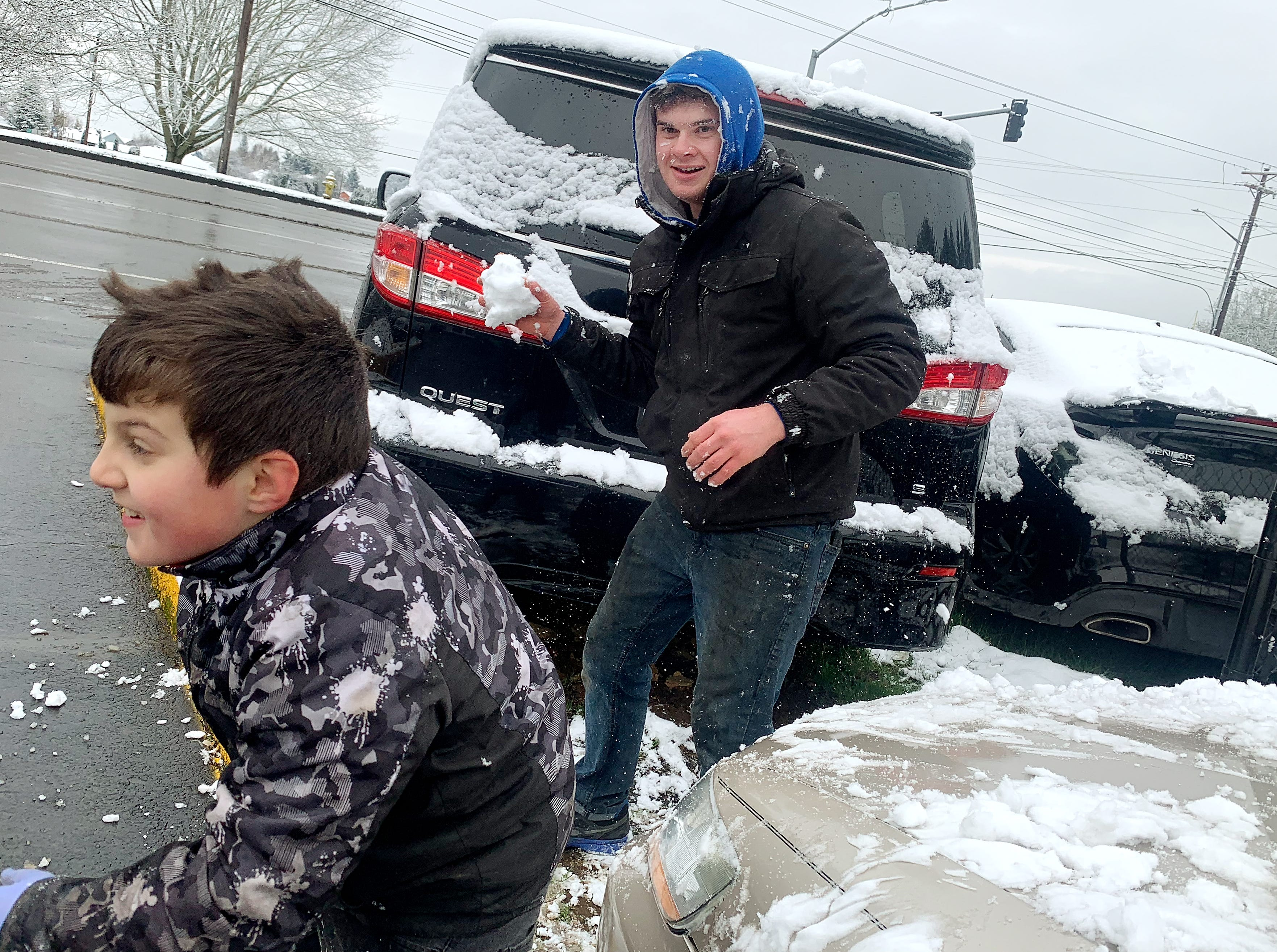 John Arabadji, 17, right, takes aim at his younger brother Sam, 8,  as they enjoy their day off from school with a snowball fight outside of the family business Tuesday, February 5, 2019 in Salem.