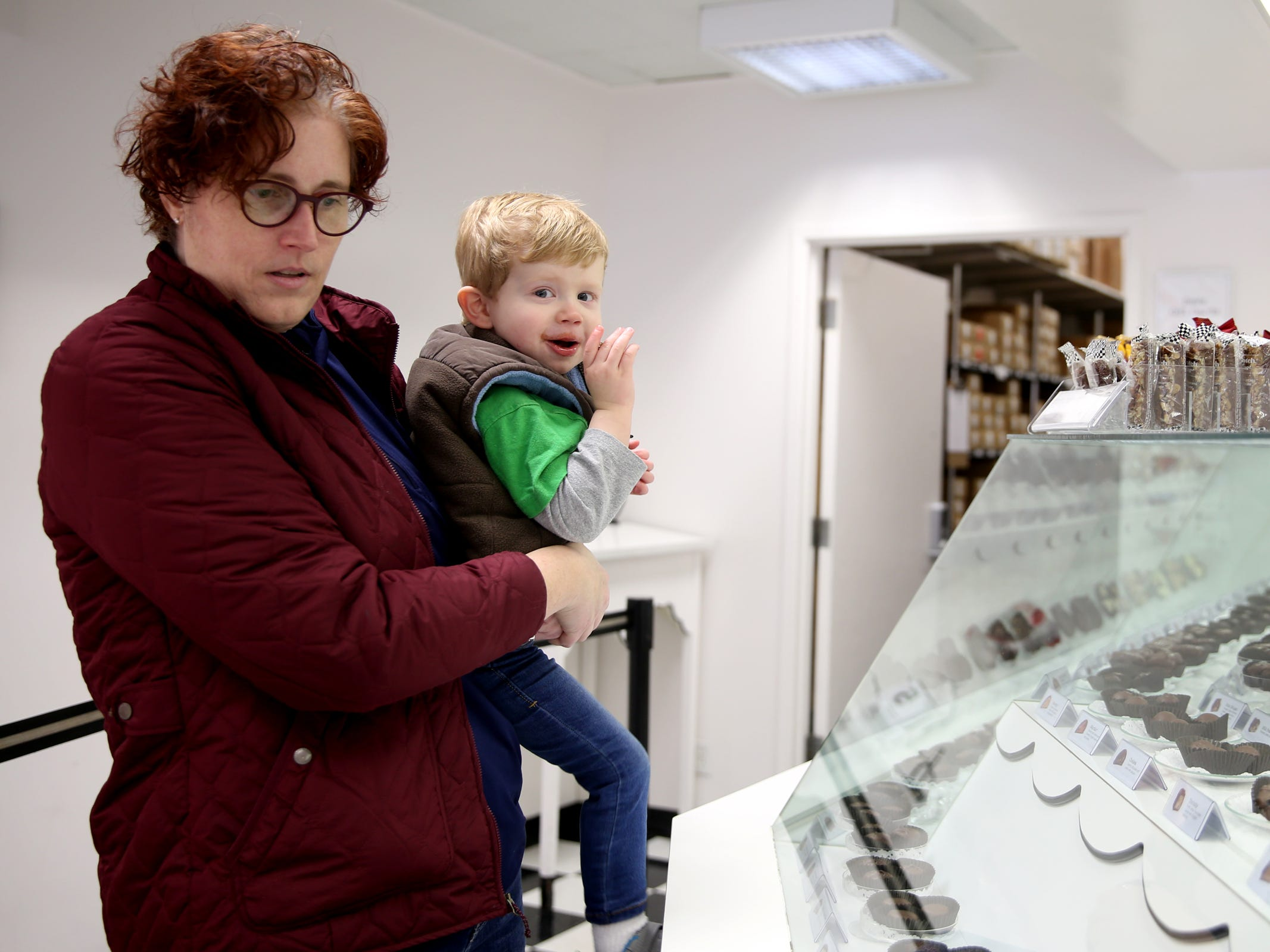 C.J. Wells, 2, nibbles on a free sample as his mom, Natalie Wells, of Salem, picks out chocolates at See's Candies in downtown Salem on Tuesday, Feb. 5, 2019.