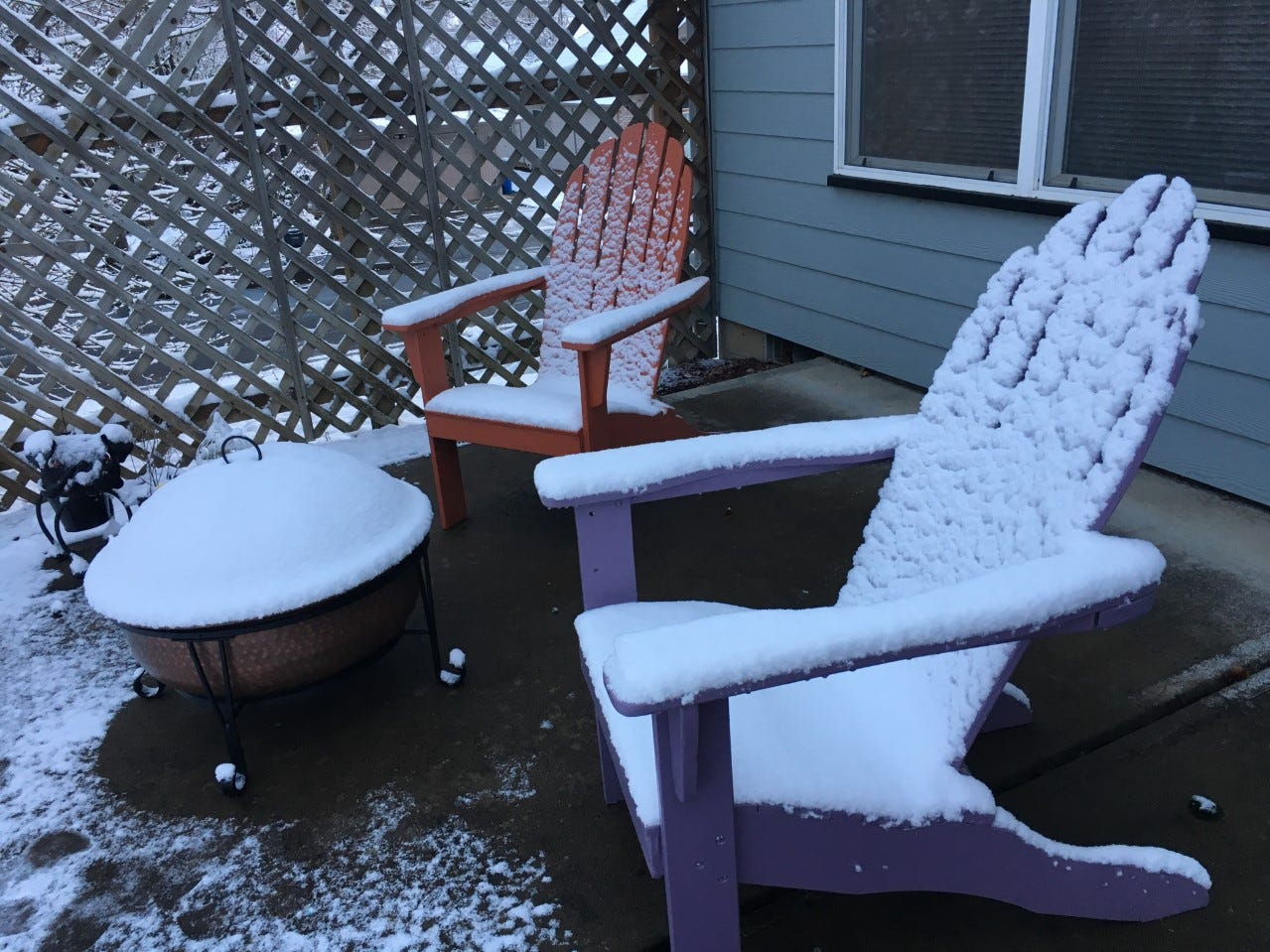 Snow covers two Adirondack chairs and a backyard fire pit in West Salem on Tuesday morning.