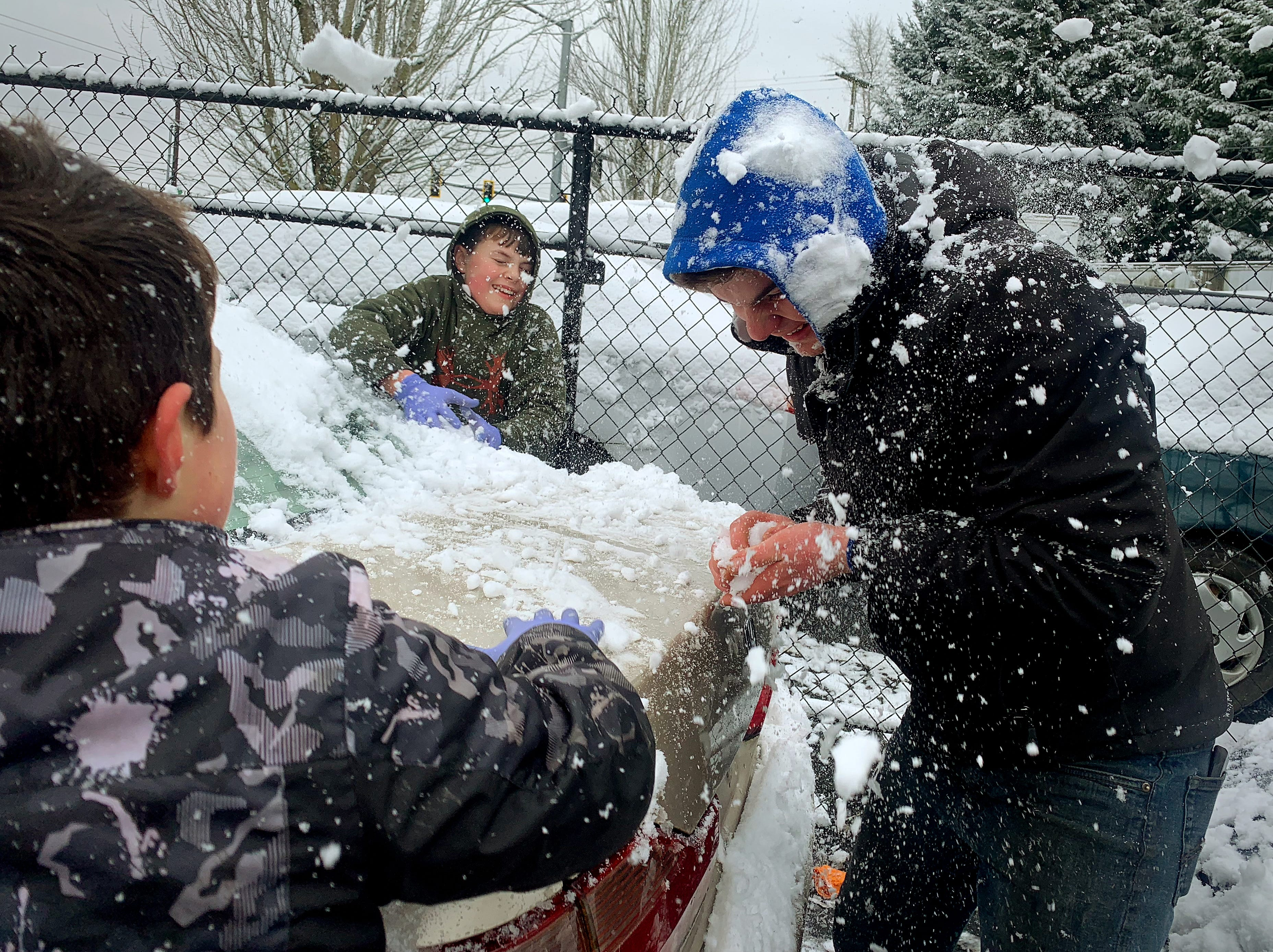 John Arabadji, 17, right, ducks to avoid snowballs from his brothers Sam, 8, left and Tim, 10, middle as they enjoy their day off from school with a snowball fight outside of the family business Tuesday, February 5, 2019 in Salem.