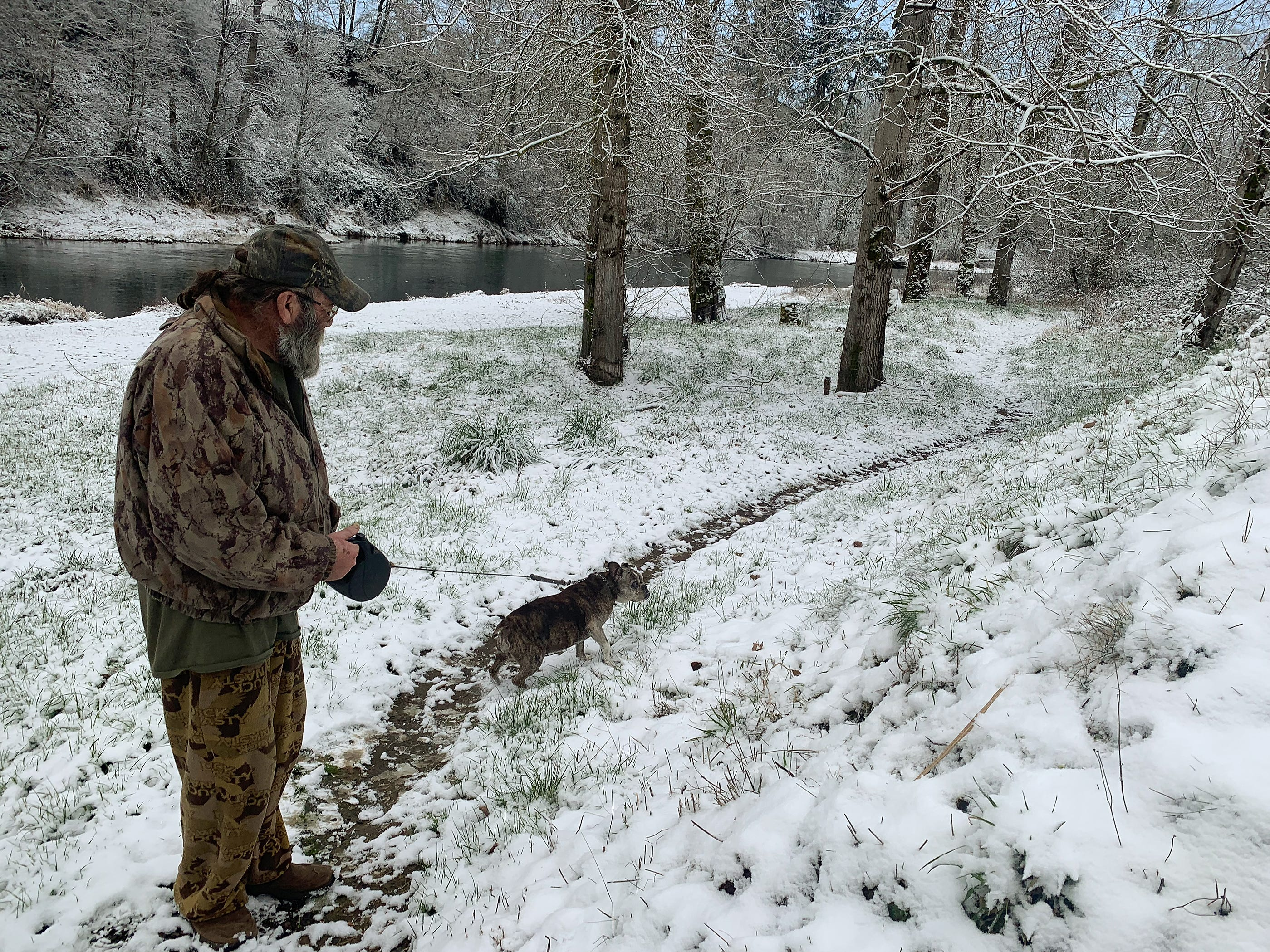 A Canby resident (who asked not to be identified) walks his dog along the Molalla River as snow covers much of the mid-Willamette valley Tuesday morning. Snow covered cars, trees and yard ornaments greeted residents of Canby, Oregon Tuesday February 5, 2019.