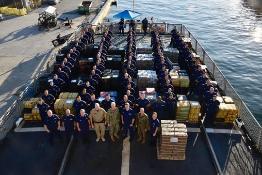 The Coast Guard Cutter Forward (WMEC-911) crew stand amongst 34,780 pounds of interdicted cocaine aboard at Port Everglades, Florida, Feb. 5, 2019.
