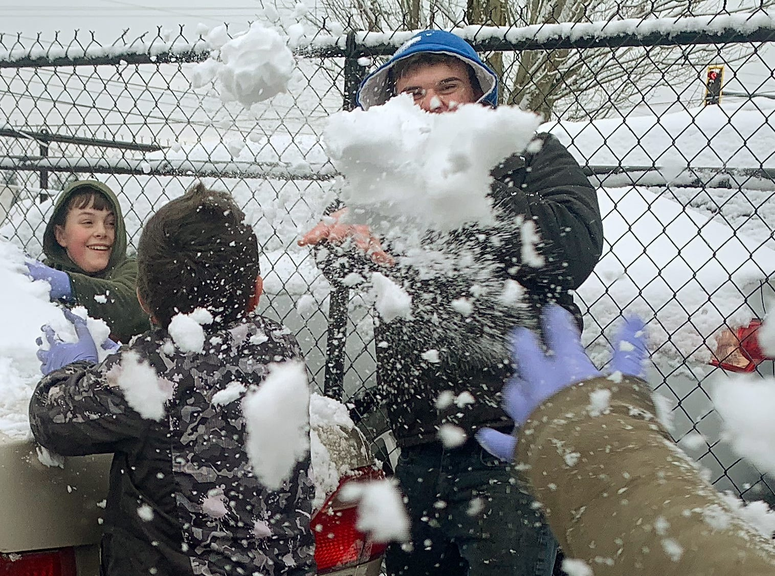 John Arabadji, 17, center, ducks to avoid snowballs from his brothers David, 13, left, 10, Sam, 8 and Tim, 10, hand at right, as they enjoy their day off from school with a snowball fight outside of the family business Tuesday, February 5, 2019 in Salem.