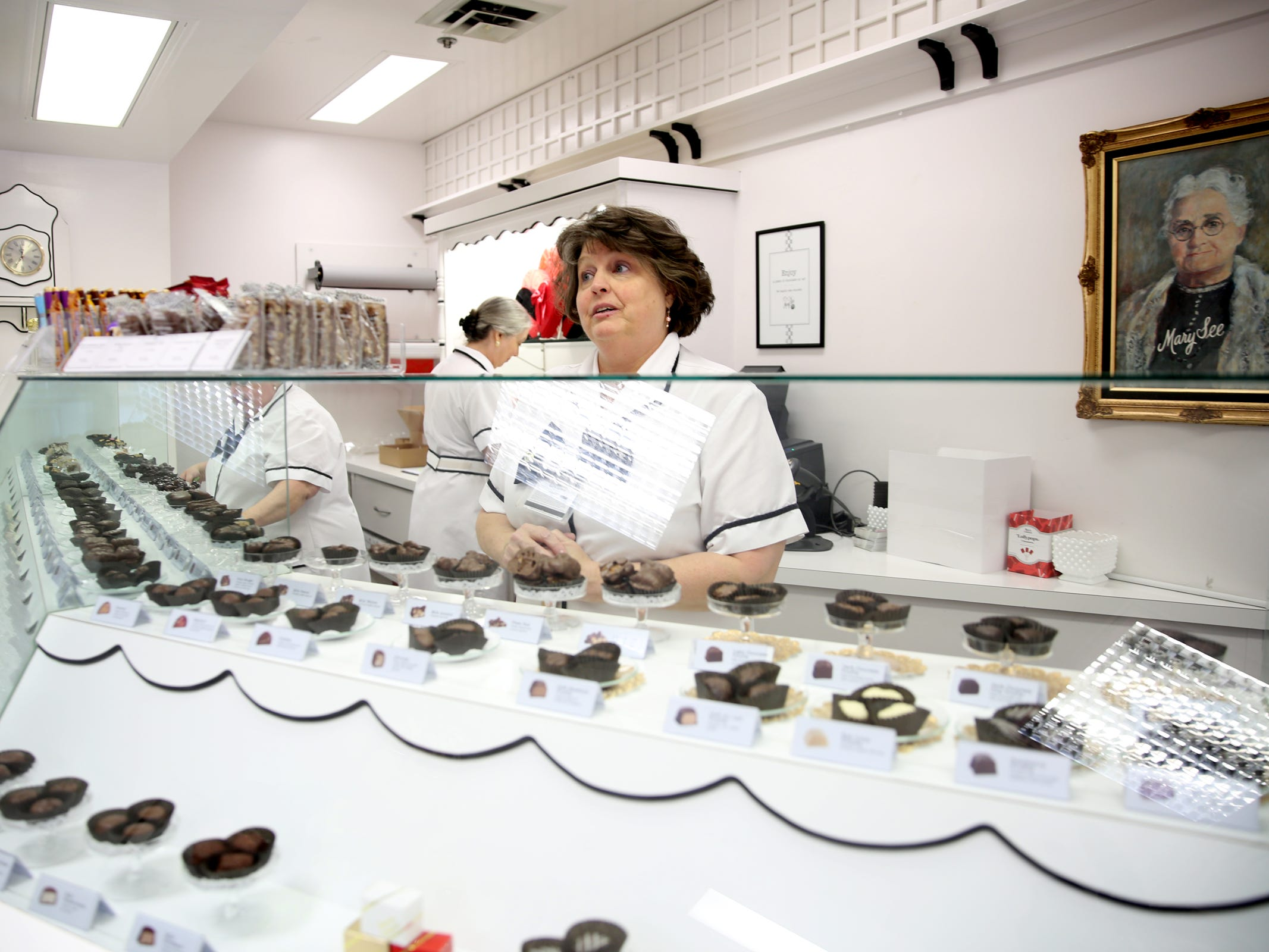 Kelly Winkle, a sales associate, helps a customer at See's Candies in downtown Salem on Tuesday, Feb. 5, 2019.