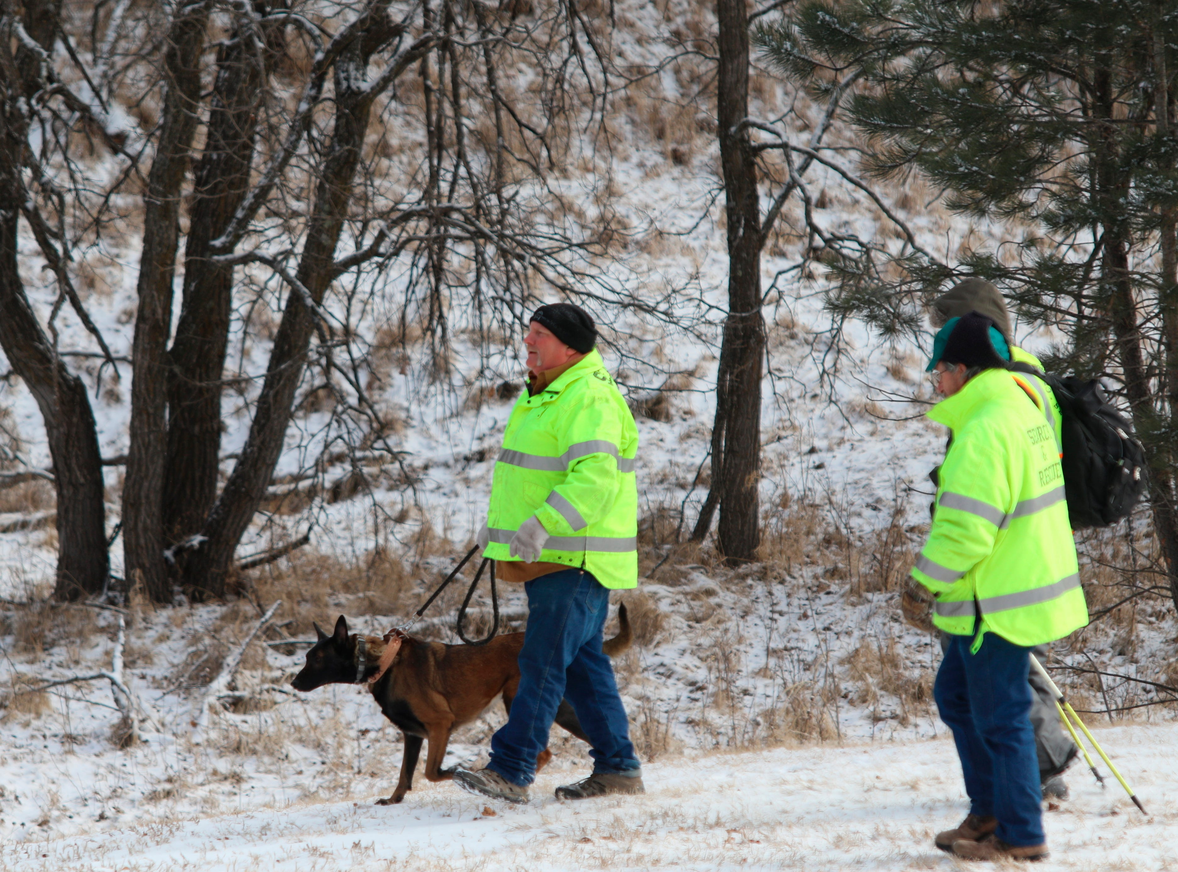A dog helps search for Serenity Dennard, 9, Monday, Feb. 4, 2019, near Rockerville, S.D. Authorities say that the girl ran away from staff at a residential youth home. (Arielle Zionts/Rapid City Journal via AP)