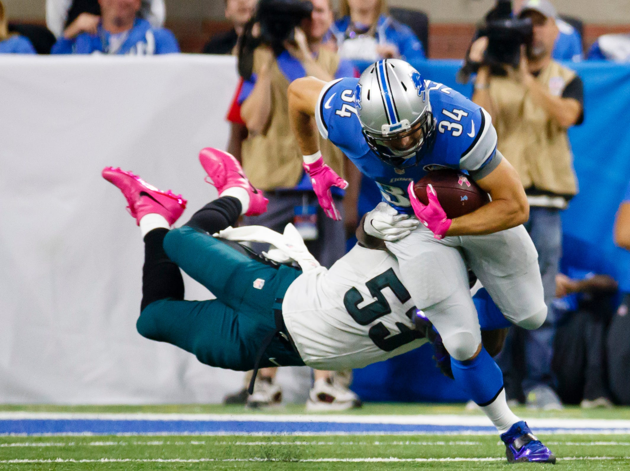 Detroit Lions fullback Zach Zenner (34) breaks a tackle by Philadelphia Eagles outside linebacker Nigel Bradham (53) during an NFL football game at Ford Field in Detroit, Sunday, Oct. 9, 2016. (AP Photo/Rick Osentoski)