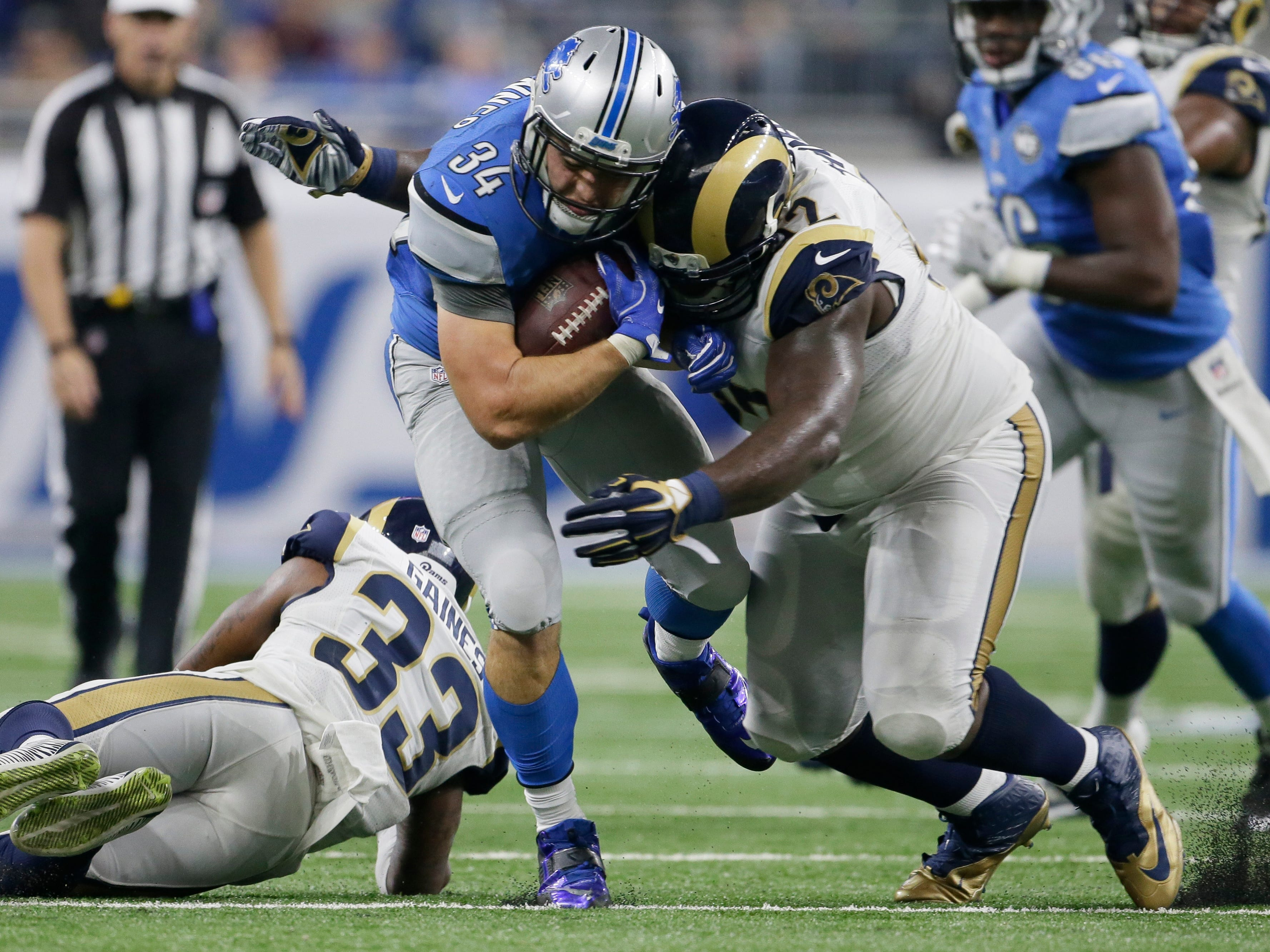 Detroit Lions fullback Zach Zenner (34) is tackled by Los Angeles Rams defensive tackle Cam Thomas during the second half of an NFL football game, Sunday, Oct. 16, 2016, in Detroit. (AP Photo/Duane Burleson)