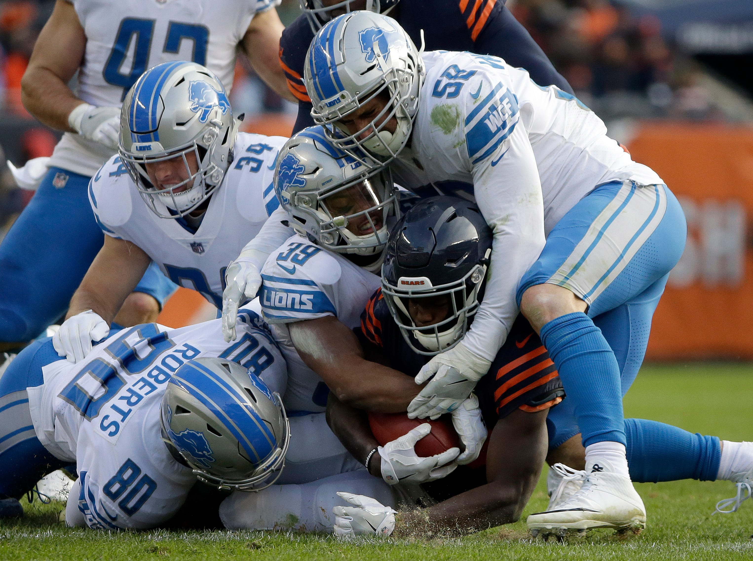 Chicago Bears' Tarik Cohen is tackled by Detroit Lions' Michael Roberts (80), Jamal Agnew (39), Paul Worrilow (58) and Zach Zenner (34) during the second half of an NFL football game, Sunday, Nov. 19, 2017, in Chicago. (AP Photo/Nam Y. Huh)