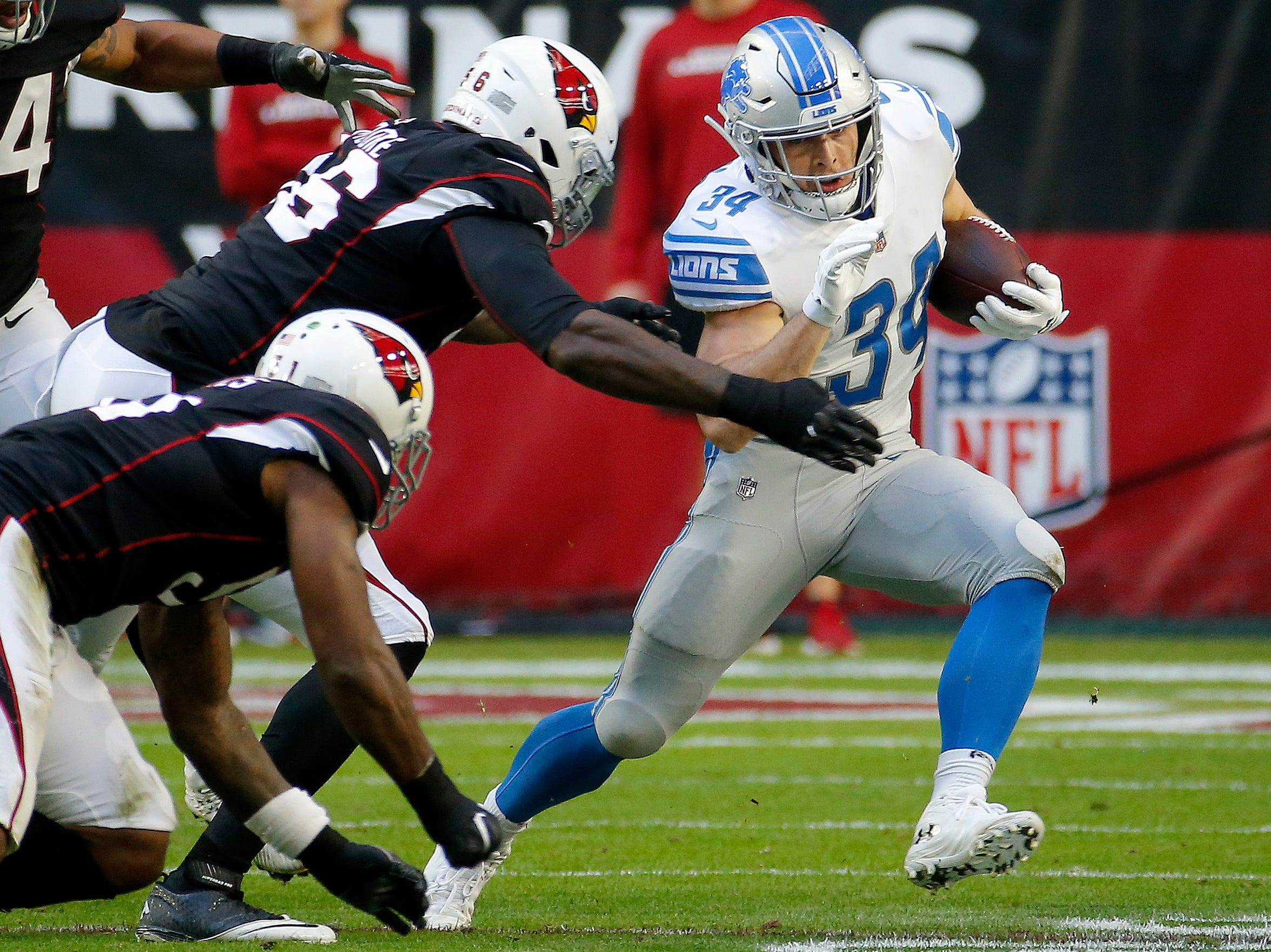 Detroit Lions running back Zach Zenner (34) tries to elude Arizona Cardinals defensive end Zach Moore (56) during the first half of NFL football game, Sunday, Dec. 9, 2018, in Glendale, Ariz. (AP Photo/Rick Scuteri)