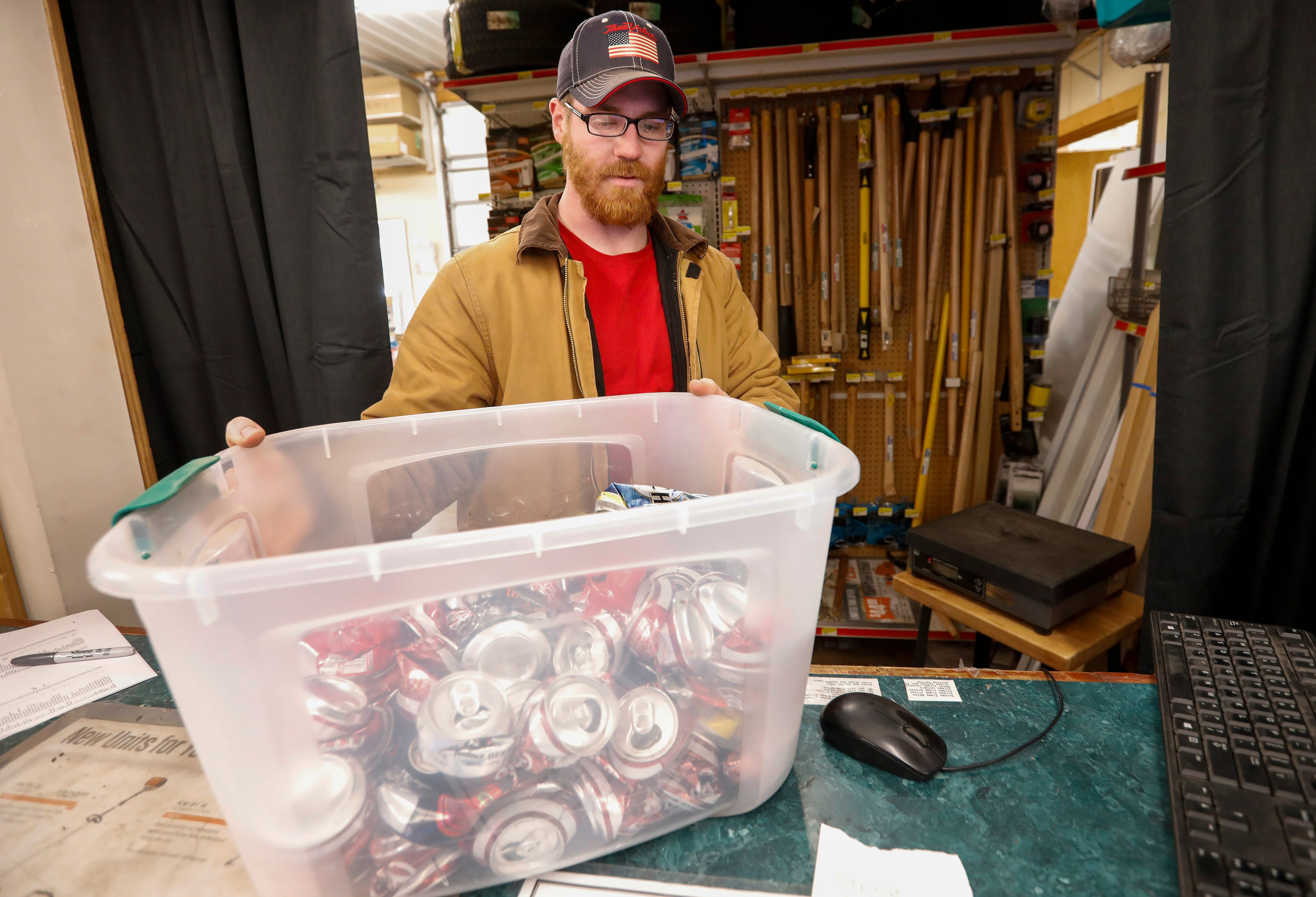 Trevor Renshaw, manager of True Value Hardware in Willard, weighs a bin of aluminum cans at his store on Tuesday, Feb. 5, 2019.
