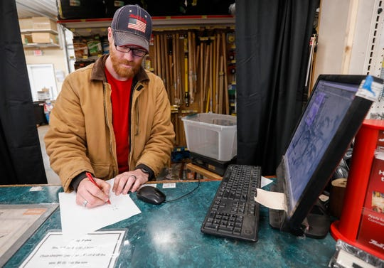 Trevor Renshaw, manager of True Value Hardware in Willard, figures out the exchange rate for a bin of aluminum cans at his store on Tuesday, Feb. 5, 2019.