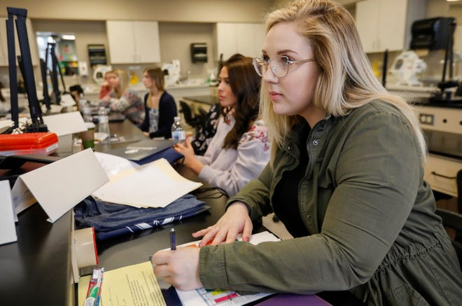 Kaitlin Denney, right, a former student at Vatterott College, listens during orientation for the dental assisting program at Ozarks Technical College.
