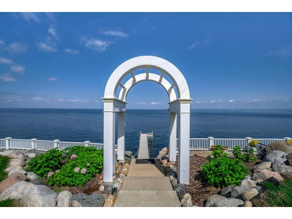 Four white pillars support an archway leading to the property's 402 feet of rock-lined Mille Lacs shoreline.