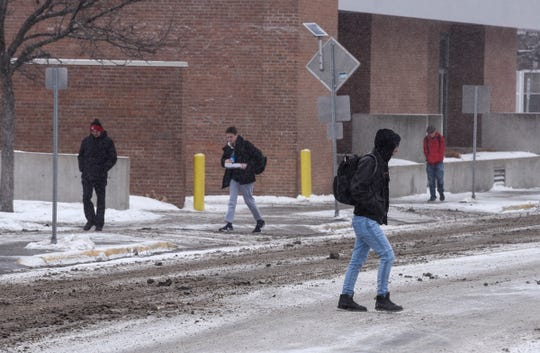 Students make their way between buildings as light snow falls Tuesday, Feb. 5, at St. Cloud State University.