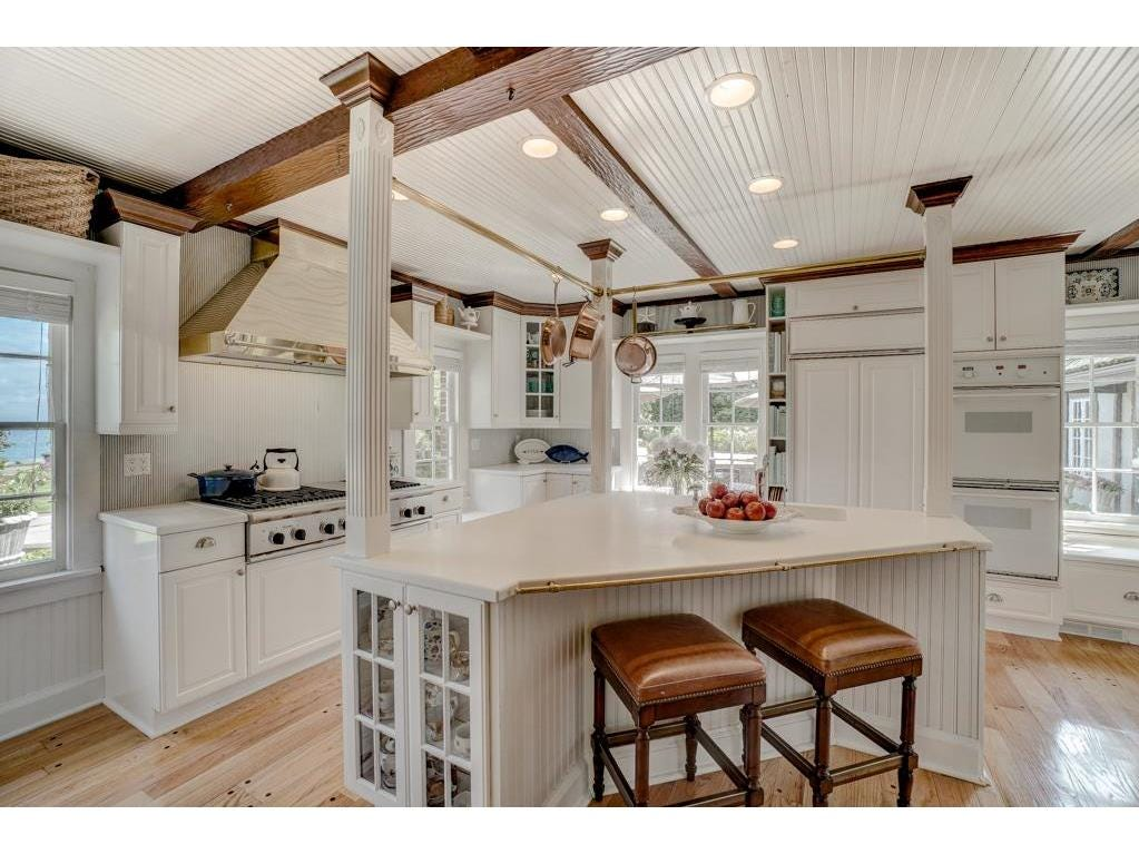 The kitchen, with multiple countertops, ample seating arrangements and a classy bright white color scheme, is a chef's dream.