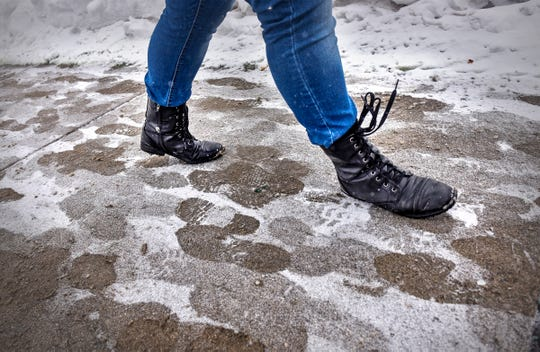 A student walks between classes as light snow falls on a sidewalk Tuesday, Feb. 5, at St. Cloud State University.