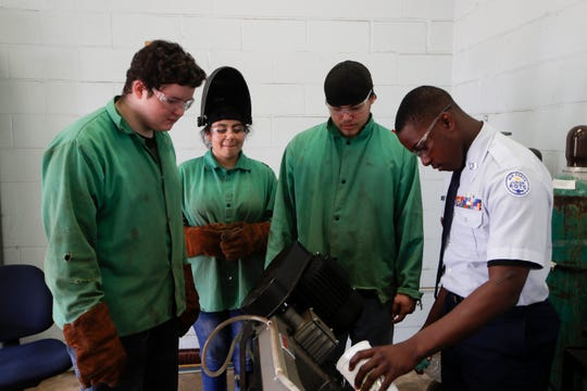 "Godby High School students Alex Connell, 16, left, Melissa Martinez, 14, Michael Smith, 16 and Landon Gardner, 17, work together to cut pieces of metal into ""coupons"" to practice welding techniques on during class Tuesday, Feb. 5, 2019."