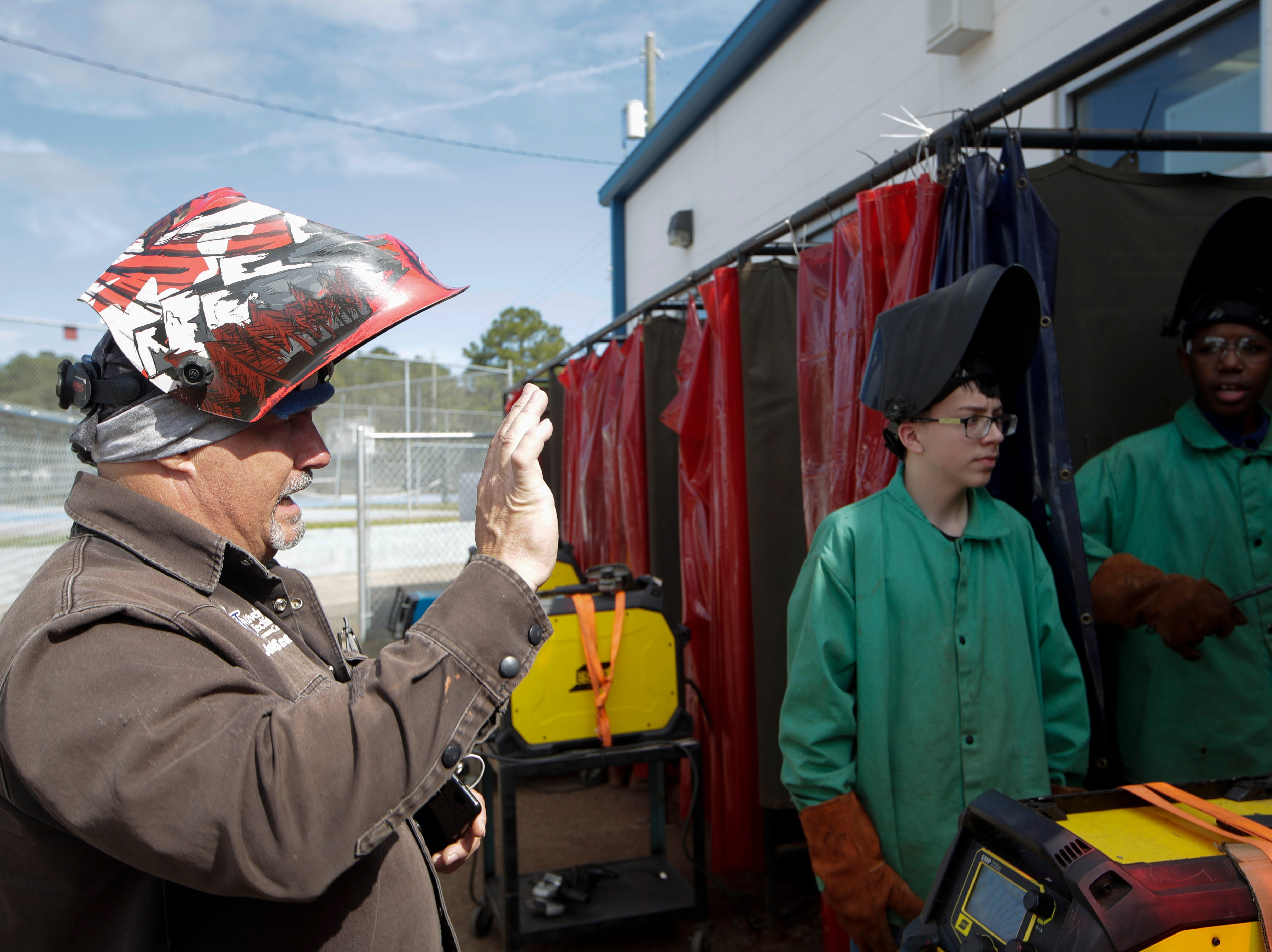 Godby High School welding instructor John Scott gives Clarence Lovett, 15, right, tips on how to weld more comfortably during class Tuesday, Feb. 5, 2019.
