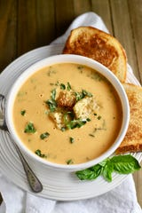 Creamy Roasted Tomato Soup is made with fresh roasted tomatoes and garnished with croutons and chopped fresh basil.