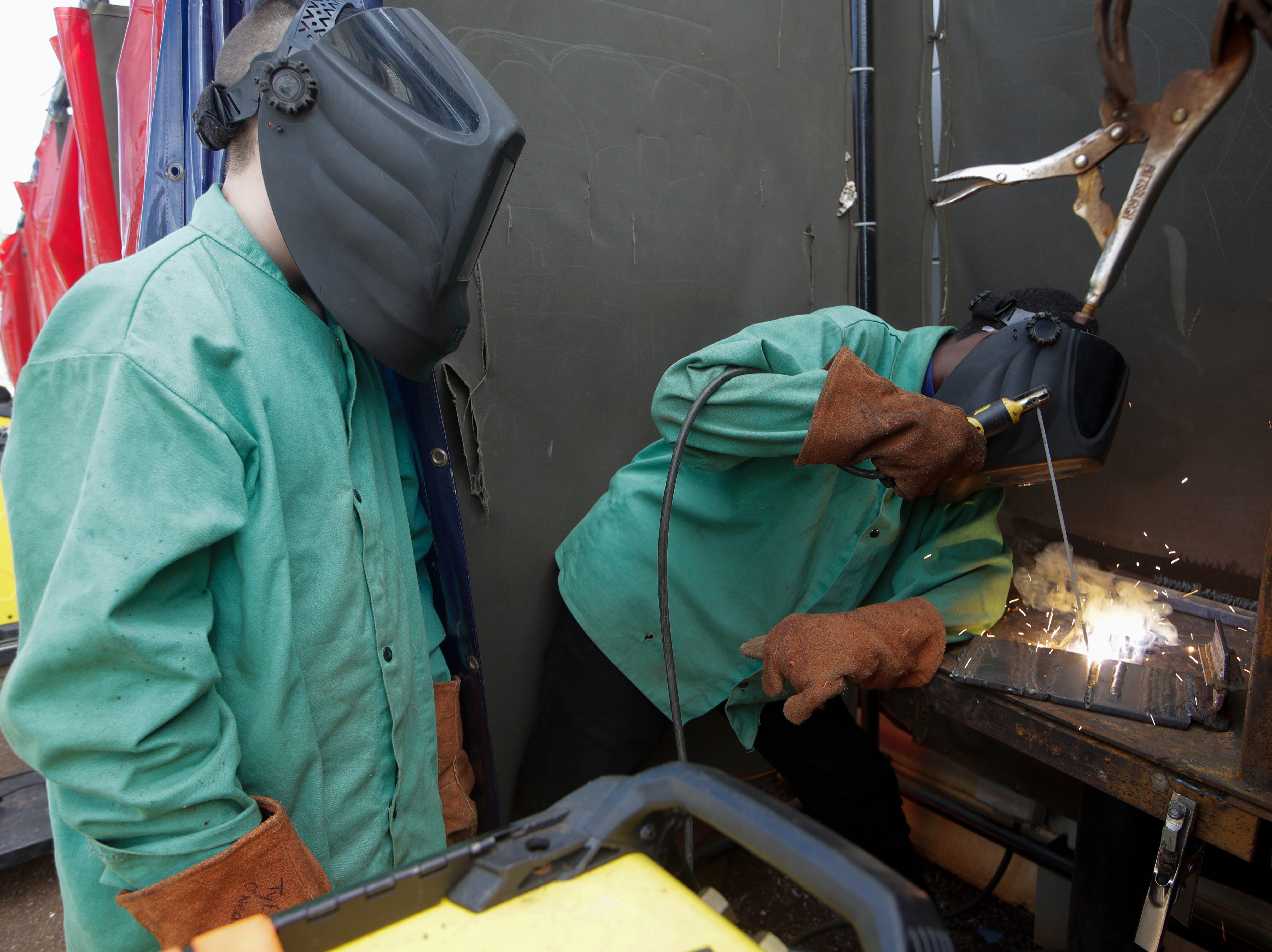 Clarence Lovett, 15, right shows Raa Middle School student Devon Gartner, 14, a flat groove weld during a welding class Tuesday, Feb. 5, 2019. Middle school students spent the class period shadowing welding students to see if they were interested in taking the course when they enter high school.