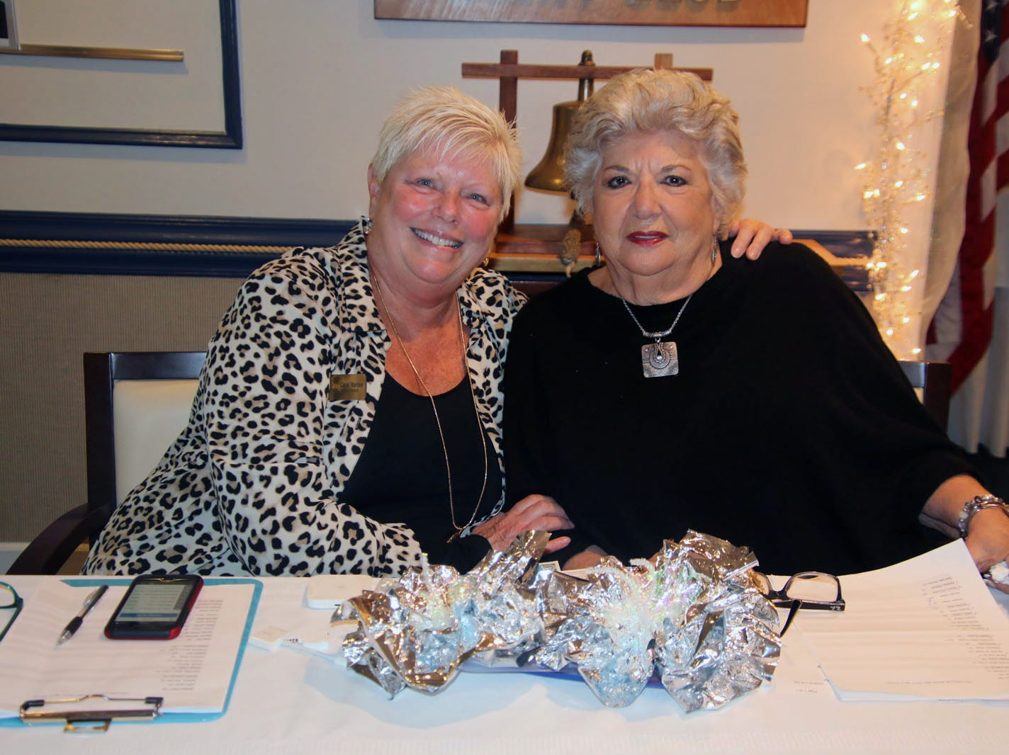 Volunteers Carol Marino, left, and Rae Tucci check people in for the Dollars for Scholars fundraiser at the Fort Pierce Yacht Club on Jan. 27.