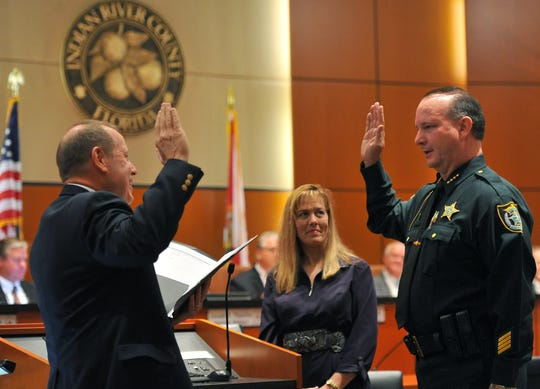 Indian River County Sheriff Deryl Loar (right) takes his oath of office from County Judge David Morgan while standing with his wife,  Jennifer, inside the County Commission chambers Jan. 8, 2013.